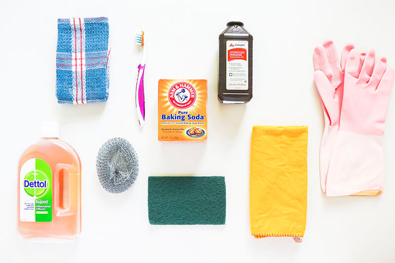 A set of kitchen tools or products on a grey table: pink gloves, dettol, baking soda, hydrogen peroxide, toothbrush, scotch brite, steel wool scrubber and kitchen towels