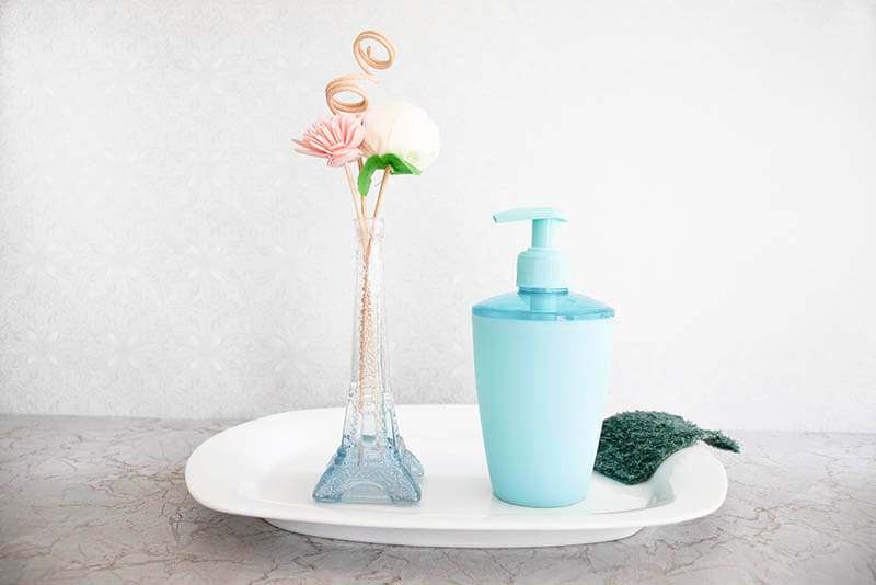 Soap dispenser or pump bottle on white plate beside green scotch brite scrubber and eiffle tower flower holder containing pink & white flowers